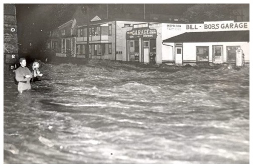 News photographer standing in waist-deep floodwaters to document 1955 flood in downtown Scranton, PA.